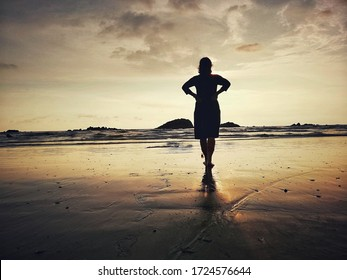 sunset in beach with beutifull refelction of a girl on wet sand