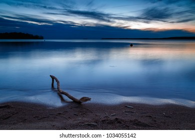 Sunset at the beach with a branch in the foreground