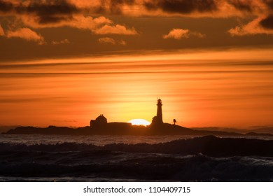 Sunset Hellstø beach with lighthouse yellow red Norway 2