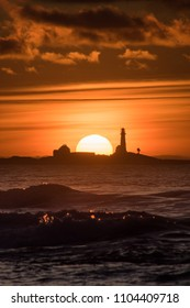 Sunset Hellstø beach with lighthouse yellow red Norway 5