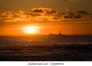 Sunset Hellstø beach with lighthouse yellow red Norway 7