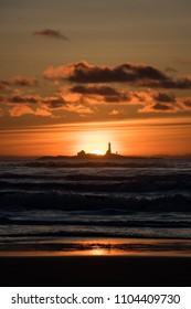 Sunset Hellstø beach with lighthouse yellow red Norway 3