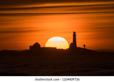 Sunset Hellstø beach with lighthouse yellow red Norway 4