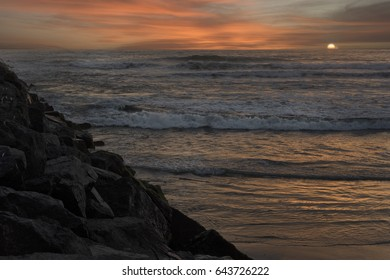 Sunset at the beach near a rockwall