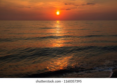 Sunset at the beach with a red sky and reflection on the waves