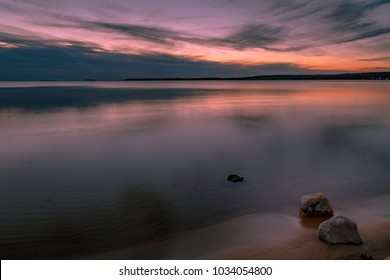 Sunset at the beach with rocks in the foreground