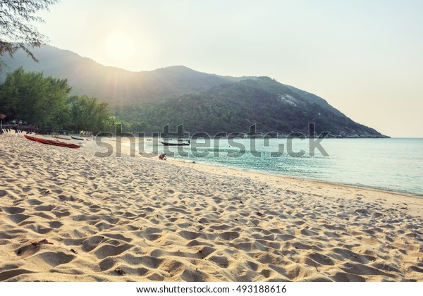 Sunset beach with white sand and kayaks