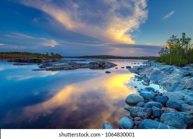 Sunset. Beautiful clouds are reflected in the water of the lake. Ladoga lake. Nature of Karelia. Northern nature in the summer. Reflection in water. Karelia. Russia.