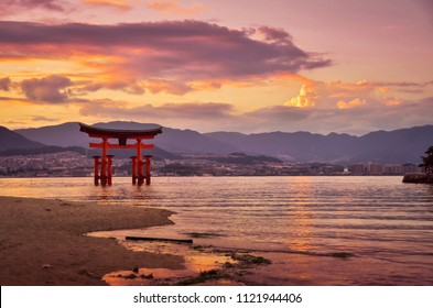 Sunset with beautiful colors. Miyajima Torii gate in front of the Shinto Shrine and with mountains in the background. It is one of the most famous gates in Japan. (Translation: Miyajima Shrine)