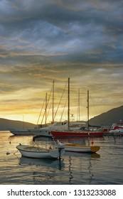 Sunset. Beautiful Mediterranean landscape with boats on water. Montenegro, Adriatic Sea, Bay of Kotor, Tivat, Seljanovo village
