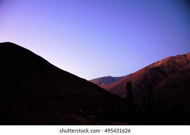 Sunset behind the black hills with a purple and blue sky in Pisco Elqui in Chile, South America