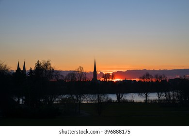 sunset behind the church towers of Luebeck, a historic tourist town in northern Germany, part of the skyline as silhouette, generous copy space in the sky