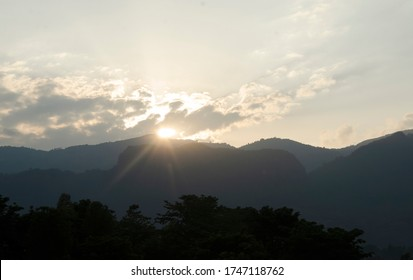 The sunset behind the clouds with dark mountain.sunset nature background.