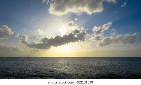 Sunset behind the clouds towards the horizon of the Atlantic Ocean