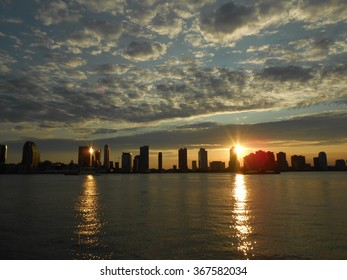 Sunset behind Jersey City, NJ - View from Battery Park in Manhattan, New York, NY.