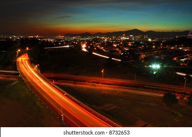 Sunset behind mountain with city light and highway as foreground.
