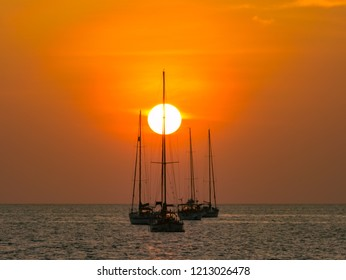 sunset behind over pole of yatch sailboat without vessel  parking on deep sea with colorful twilight evening sky background seascape.