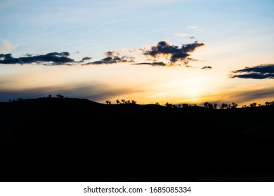 Sunset behind silhouette of hill and trees