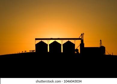 Sunset behind storage silos. Machinery silhouette. Grain storage. Curitibanos, Santa Catarina / Brazil