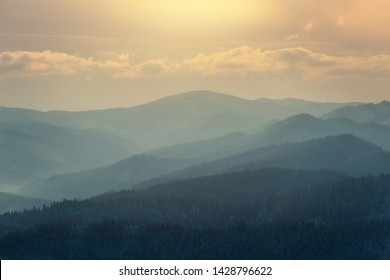 Sunset in the Beskydy Mountain National Park. The sky is orange and yellow with a long, low cloud. The foreground is layers of mountains, hills, and ridges with barren trees in winter