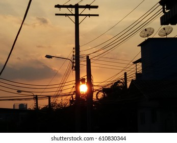 Sunset Between Two Communication Poles in the City Suburbs with Wires and Satellite Dishes Nonthaburi Province Thailand
