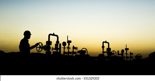Sunset blue hour and silhouette of oilfield worker at oil well manifold