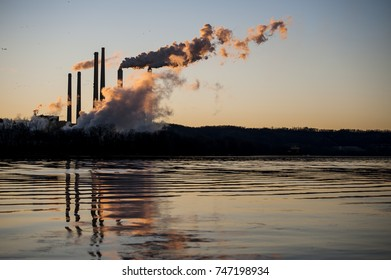 A sunset / blue hour view of numerous smokestacks and emissions coming from a coal fired power plant in Kentucky across the Ohio River.