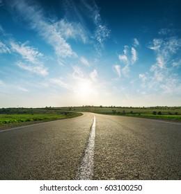sunset in blue sky over asphalt road