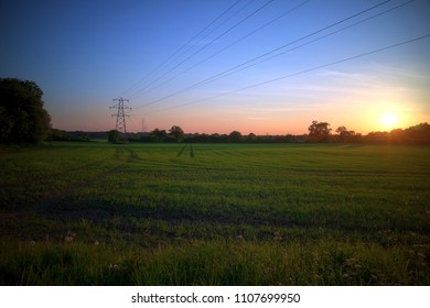 Sunset with blue sky over green field, with pylon and electricity lines outlined against horizon.