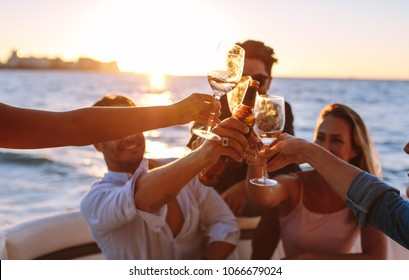 Sunset boat party with young people toasting drinks. Group of men and women having a boat party.
