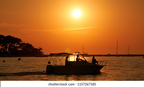 Sunset with boats on the coast of the city Porec in Croatia. In the background is the island Sveti Nikola