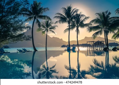 Sunset in Bora Bora , French Polynesia . Palm trees and Mount Otemanu reflected in the pool. Retro style color tones.