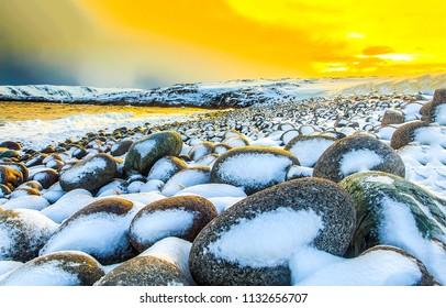 Sunset boulders beach snow landscape. Snow covered boulders beach sunset panorama. Sunset snow covered boulders beach view
