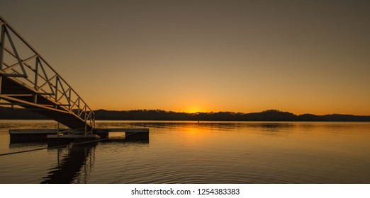 Sunset bridge to a fishing pier at Dale Hollow Lake, Tennessee. Beautiful orange and yellow sunset reflected in calm water. Concepts of travel, tourism, vacation, and relaxation