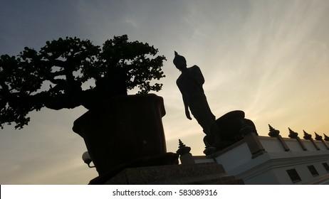sunset with Buddha statue and bonsai