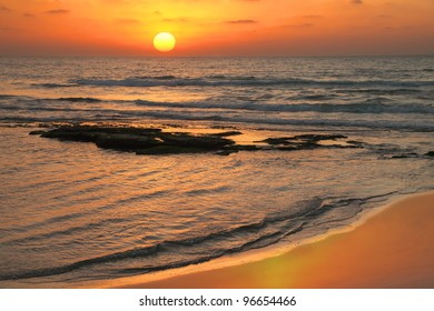 Sunset by the Mediterranean sea and its color reflection on wet sand of coast. Tel-Aviv. Israel