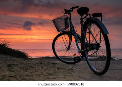 Sunset by the ocean with a cycle in the foreground in Skagen Denmark