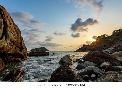 Sunset by a rocky beach in an island off Karwar, Karnataka in India