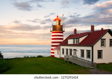 """Sunset by West Quoddy Head lighthouse, with its red and white stripes, referred to as the """"candy cane"""" lighthouse, in down east Maine, in New England. It is located in the easternmost point in USA."""