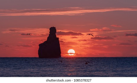 Sunset in Cala Benirras with red sky , Ibiza , Spain