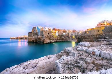 Sunset at Cala Paura gulf with Bastione di Santo Stefano in village on the rocks Polignano a Mare, Apulia, Italy, province of Bari.