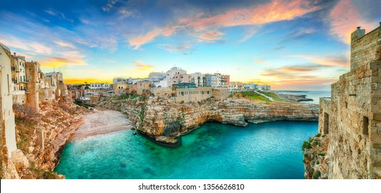Sunset at Cala Paura gulf with Bastione di Santo Stefano and Lama Monachile beach in background. Polignano a Mare, Apulia, Italy, province of Bari.