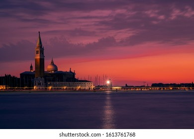 Sunset at the canal grande close to San Marco square in Venice Italy, with a famous church in the background and lighthouse.