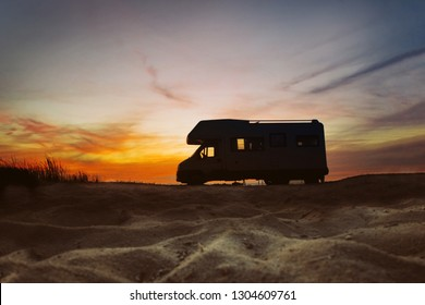 Sunset and caravan silhouette. Van life concept. Travelling in the Europe. Camper van on the beach.