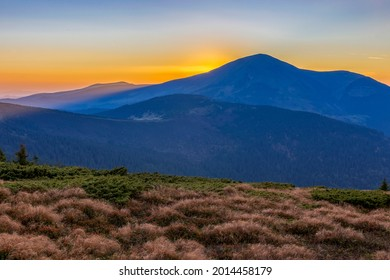 Sunset in the Carpathian mountains. Sun disk and long rays at sunset on the mountain top. Picturesque sunset in the mountains.Vibrant photo wallpaper. Petros Mountain (2020 m), Chornohora ridge.