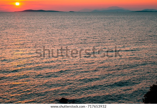 Sunset casting orange yellow and pink hues over Greek Mediterranean with islands in the background