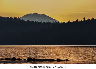 Sunset casts glow on calm waters of Alpine lake in Lassen Volcanic National Park