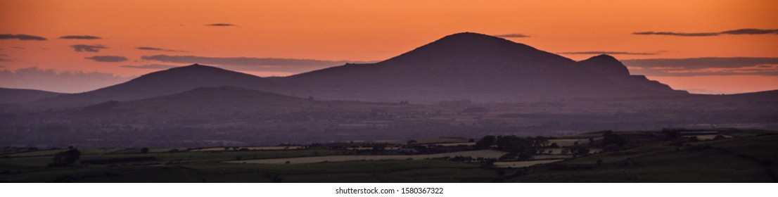 The sunset casts a red sky over the mountains of Yr Eifl on the Lleyn Peninsula in north Wales, viewed from Moel-y-Gest in Snowdonia National Park.
