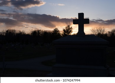 Sunset at the cemetery with cross stone