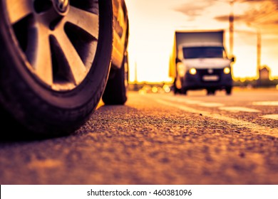 Sunset in the city, the approaching van on the highway. Close up view from the level of a parked car wheels, image in the orange-purple toning